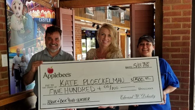 "Robert Force, general manager of the Port St. Lucie Applebee's, left, and Alexis Demarest, manager of the Port St. Lucie Applebee's, present a check for $500 to Northport K-8 teacher Kate Ploeckelman, who was announced as a winner of Applebee's Above and ""BEE""yond Teacher Contest."
