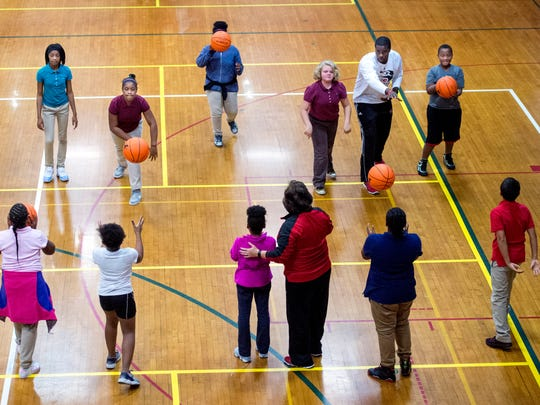 Jon Harris, Southern Illinois University Edwardsville Men's Basketball head coach, top right, instructs students on passing techniques during the Ohio Valley Conference Basketball Youth Clinic at the downtown YMCA in Evansville, Ind., on Monday, Oct. 23, 2017. The free clinic, coached by 11 OVC head coaches, hosted 75 local 4th-6th grade students who had shown great character, good behavior, and leadership within their after school programs.