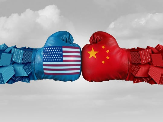 Two boxing gloves one with the U.S. flag, the other with China's flag