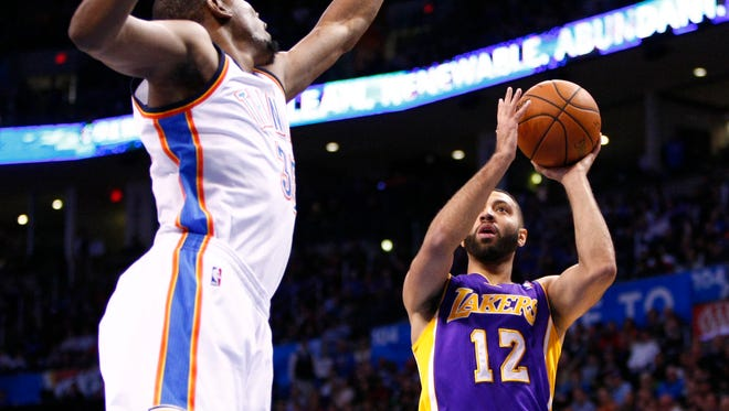 Los Angeles Lakers guard Kendall Marshall (12) tries to shoot over Oklahoma City Thunder's Kevin Durant on March 30, 2014, in Oklahoma City.