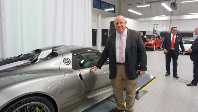 Parsippany Mayor James Barberio admires a $1.5 million 918 Spyder sports car at the grand opening of the new Paul Miller Porsche dealership on Route 46 in Parsippany.