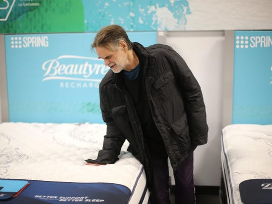 Dec. 14, 2015: Jonathan Kovac checks the firmness of a mattress at Value City Furniture in Springdale. For 15 years, Jonathan Kovac had been mostly drunk and, when not in jail on some charge or another, living on the streets of Clifton. But last Christmas, Greater Cincinnati Behavioral Health Services found him a home. Now, he says he drinks less and his family says that they have a better relationship with him.