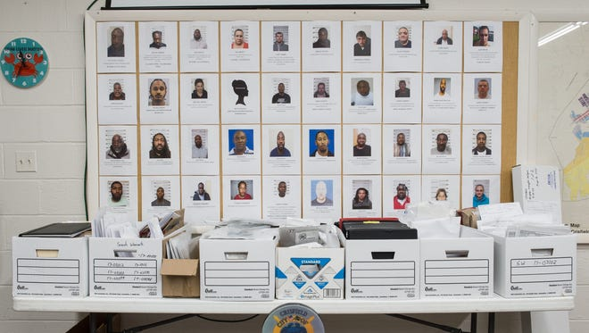 A view of several boxes containing evidence as well as photos of people who were arrested.