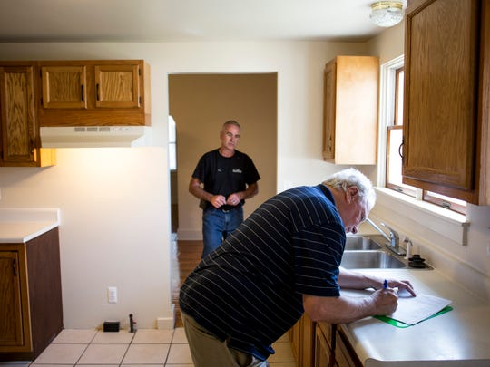 Landlord Bill Johnson chats with Michigan State Housing Development Authority inspector Joe Melcher Wednesday, June 14, 2017 at one of his properties on 13th Street in Port Huron.