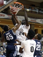 In this Nov. 20, 2016 file photo, Central Florida's Tacko Fall (24) dunks over the defense of Villanova's Darryl Reynolds (45) during the first half of an NCAA college basketball game at the Charleston Classic at TD Arena in Charleston, S.C.