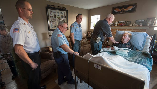 Robert Knaub, right, with West Manchester, leans over to greet Marshall Woodward as a line of fire fighters file though his home to wish him well. Williams says he remembers Woodward riding his bicycle to fires as a junior. About 25 pieces of equipment from 10 fire companies converge at the home of Marshall Woodward Sunday October 25, 2015 as a special tribute. Woodward was diagnosed with brain cancer in March 2011 and was recently bedridden. Woodward, age 55, was a former fire chief of Lincolnway Fire Company and started as a junior firefighter at age 13 at Shiloh.