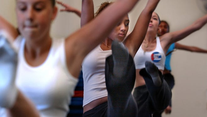 Xiomara Medina, 15, center, looks out from her row during a leg kick to the hip hop song Hey Baby along with Jennifer Baldino, 14, front, and Janel Gomez, 15, during the St. Lucie Miss-Ettes summer dance camp. This image was taken in June 2004.
