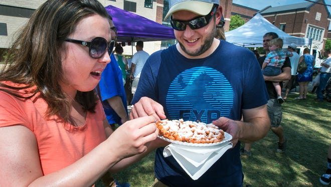 Krista, left, and Michael Kepler of Mechanicsburg feast on Savory's Pumpkin Funnel Cake in 2015. The festival is expected to bring in 15,000 people.