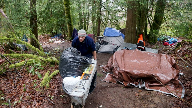 """A resident at a former homeless camp on Almira Drive in East Bremerton uses a wheelbarrow to help clean up an encampment before it was cleared in 2018. Kitsap County officials are looking for funding and a location to site a 75-bed """"Navigation Center."""""""