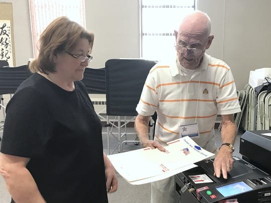 Poll worker George Everett helps resident Sue McCarty scan her ballot Tuesday at the Horseheads Village Hall.