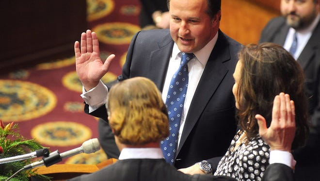 """FILE - In this Jan. 7, 2015, file photo, John J. Diehl Jr., center, is sworn in as the Speaker Pro Tem of the House of Representatives during the opening of the Missouri legislature in Jefferson City, Mo. Diehl apologized Wednesday, May 13, 2015, for his """"poor judgment"""" following a newspaper report that he had exchanged sexually charged text messages with a college student who was serving as a Capitol intern. (Don Shrubshell/The Columbia Daily Tribune via AP, File)"""