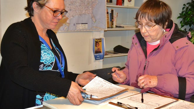 Denise Weldon-Siviy, candidate for State Rep. (91st District), gives her petition to a voter.