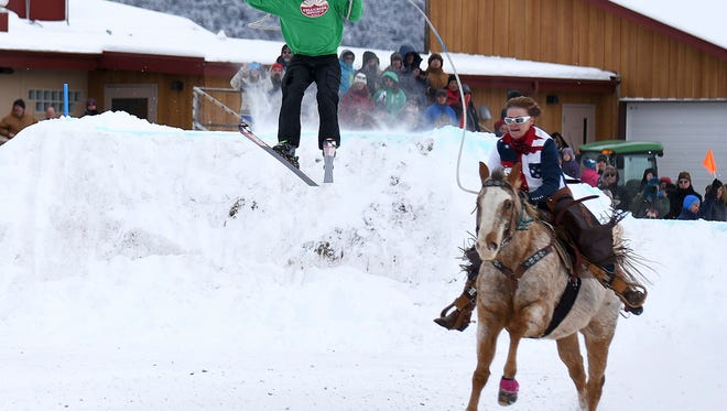 This photo taken Jan. 7, 2017, shows Clarissa Dahl, riding Rage, pulling Shawn Gerber at the first-ever skijoring event in Ridgway, Colo. In this fascinating and unique winter sport, horse and rider pull a skier over jumps and through slalom gates.(Dale Shrull /The Grand Junction Daily Sentinel via AP)