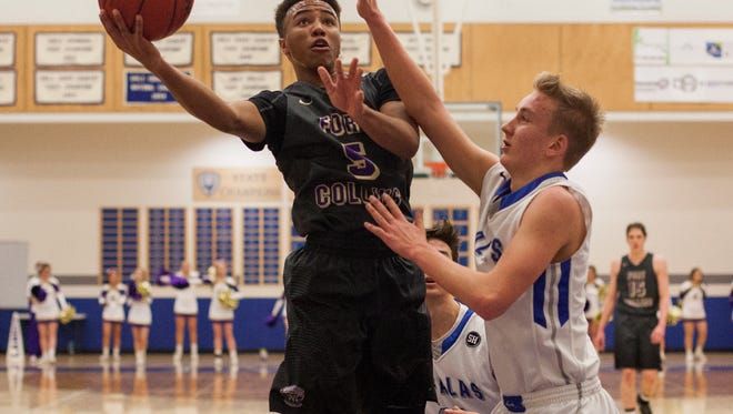 Fort Collins senior Iseri Palacio (5) gets a shot against Poudre's Jack Fisher (55) Tuesday  at Poudre High School in Fort Collins. Fort Collins won the game, 50-42.