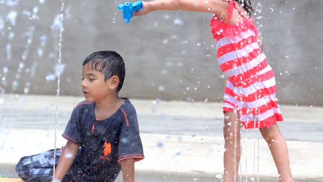Judy Torres, 3, empties a water pistol on Jacob Delgado, 5,  the Penn Park Splash Pad Friday, June 9, 2017. Both live in York City. The attraction opened this week and will remain open throughout the summer weather permitting. Hours are 11 a.m. to 7 p.m. daily. Bill Kalina photo