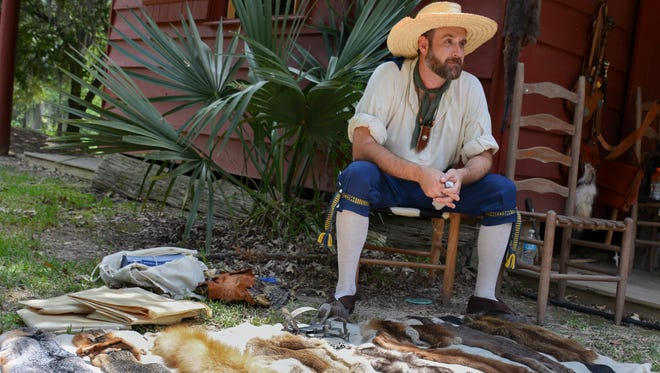 A volunteer displays dried fur pelts during 2015 Acadian Culture Day at Vermilionville.