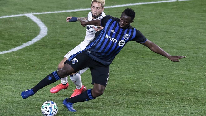 Revolution forward Diego Fagundez, rear, defends against Montreal Impact midfielder Victor Wanyama during the second half Wednesday night at Red Bull Arena in Harrison, New Jersey.