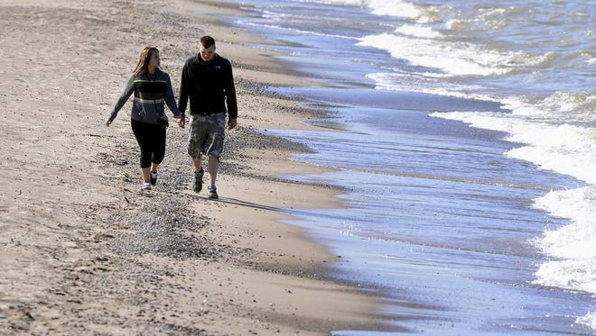 A couple walks on the beach on  Lake Huron in Michigan's Thumb in June.