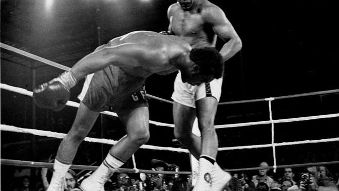 Challenger Muhammad Ali watches as defending world champion George Foreman goes down to the canvas in the eighth round of their WBA/WBC championship match in Kinshasa, Zaire, on October 30, 1974. Foreman is counted out by the referee and Ali regains the world heavyweight crown by KO in the bout dubbed 'Rumble in the Jungle.'