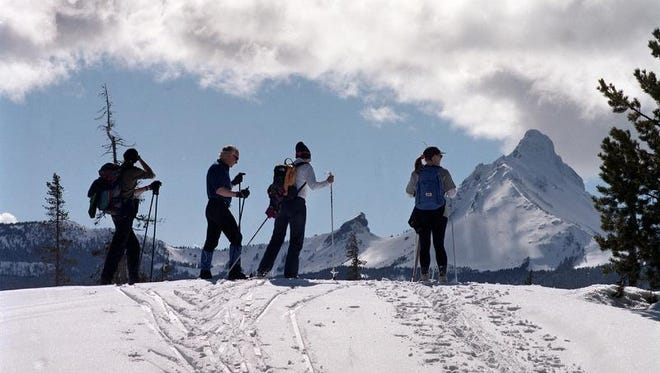 A group of skiers stands in front of a mountain skyline at Ray Benson Sno-Park.