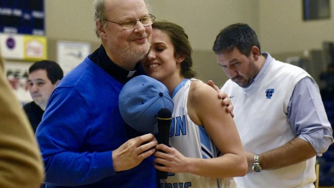 Fr. Mike Coleman hugs Serena Berrey after they sang the national anthem before a basketball game Feb. 7, 2017, at Tolton High School. Coleman, who serves as the Trailblazers' chaplain, recently announced his cancer diagnosis and was scheduled to undergo surgery Wednesday.