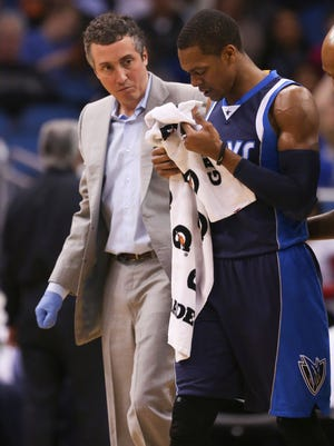 Mavericks guard Rajon Rondo walks off the court with a trainer after being kneed in the face.