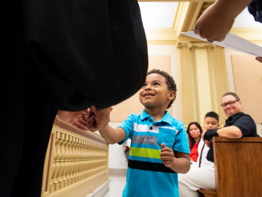 Adrel Acosta, 4, shakes Common Pleas Judge Clyde W. Vedder's hand after he and his mother, Maria Cabreja, became U.S. citizens. Cabreja and her son emigrated from the Dominican Republic.