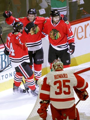 Chicago Blackhawks' Ryan Hartman, top center, celebrates his goal with Tyler Motte (64) and Marcus Kruger as Detroit Red Wings goalie Jimmy Howard watches during the first period of a preseason game, Tuesday, Oct. 4, 2016, in Chicago.