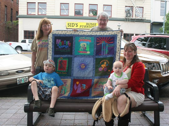Standing: Mary Ann and Hersch Sangster hold up a quilt made from T-shirts of previous Monster Cookie Bicycle Rides while their grandchildren, from left, Axel Hansen, 4, and Titus Hansen, 7 months, pose with their mom Mandi Hansen. The annual Monster Cookie Metric Century Bicycle Ride is Sunday, April 26.