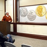 In this Nov. 30, 2015 photo, Henry Sweets, executive director of the Mark Twain Boyhood Home & Museum in Hannibal, Mo., unveils the design for commemorative gold and silver Mark Twain coins that will be sold starting next year. Some of the proceeds of the coin sales benefit four Twain-related sites, including the Hannibal home and museum.