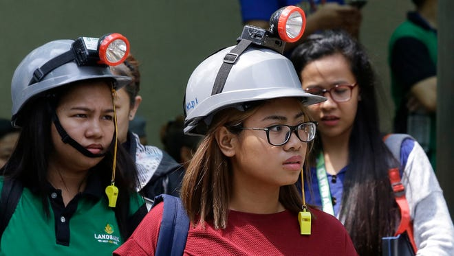 Office workers wear protective gear as they evacuate their building after an earthquake was felt in Manila, Philippines on Friday, Aug. 11, 2017. The Philippine Institute of Volcanology and Seismology said the earthquake's epicenter was three miles southwest of Batangas province's Lian town at a depth of 107 miles. Office workers in the capital left their buildings but no damage was apparent after the quake struck about midday Friday.