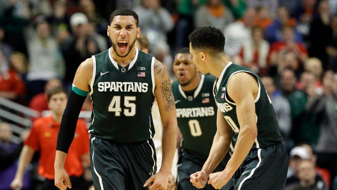 Michigan State's Denzel Valentine (45),  Marvin Clark Jr. (0) and  Travis Trice (20) celebrate as they took the lead against Maryland in the second  half of an NCAA college basketball game in the semifinals of the Big Ten Conference tournament in Chicago, Saturday, March 14, 2015.