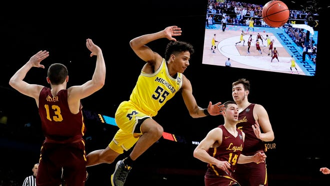 Michigan guard Eli Brooks (55) fights for a rebound with Loyola-Chicago's Clayton Custer (13) and Ben Richardson (14) during the first half in the semifinals of the Final Four NCAA college basketball tournament, Saturday, March 31, 2018, in San Antonio.