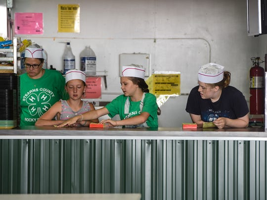 4-H'ers get ready to take orders at the 4-H food stand during the first day of the Stearns County Fair Wednesday, July 26, in Sauk Centre.