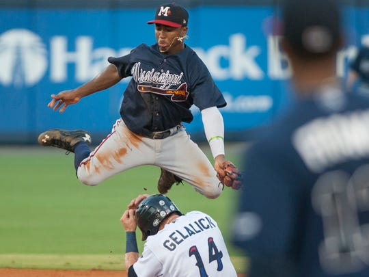 Jeff Gelalich (14) safely slides under a leaping Ozzie Albies (20) as the ball is over thrown during the Mississippi Braves vs. Blue Wahoos baseball game at Blue Wahoos Stadium in Pensacola, FL on Wednesday, August 3, 2016.