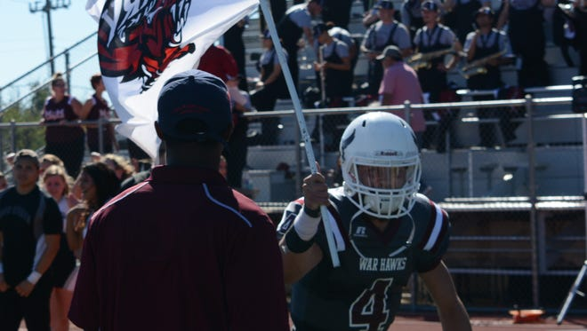 McMurry quarterback Kevin Hurley Jr. runs with a War Hawk flag after the team's 42-30 homecoming win over Belhaven on Saturday at Wilford Moore Stadium.