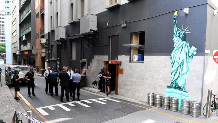Police officers are seen at a cordoned off area after a man was accidentally shot in Eagle Lane in Brisbane's central business district, Queensland, Australia, Jan. 23, 2017.