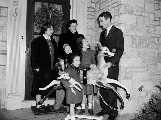 "Robert May, right, a Chicago advertising writer and his family, pose with his creation ""Rudolph the Red Nosed Reindeer"" in front of their home in Skokie, Ill., Dec. 19, 1949. May dreamed up ""Rudolph"" in 1939, at the request of his boss. The firm used the fable in verse as a Christmas promotion. Now, Rudolph has become famed in verse,song and as a holiday TV special and is also known all over the world. With May are his wife and their four childern  Barbara, 15, Chirstopher, 7, Ginger, 4, and Joanna, 8. (AP Photo/Ed Maloney)"