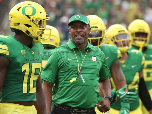 FILE - In this Sept. 2, 2017, file photo, Oregon coach Willie Taggart, center, joins his team as they take the field for an NCAA college football game against Southern Utah in Eugene, Ore.  When Taggart got the coaching job at Oregon, one of the first calls he made was to Stanford coach David Shaw. The two had spent three years together as assistants under Jim Harbaugh for the Cardinal, forging a friendship that carries over into their first meeting as adversaries on Saturday night when No. 23 Stanford hosts the Ducks. (AP Photo/Chris Pietsch, File)