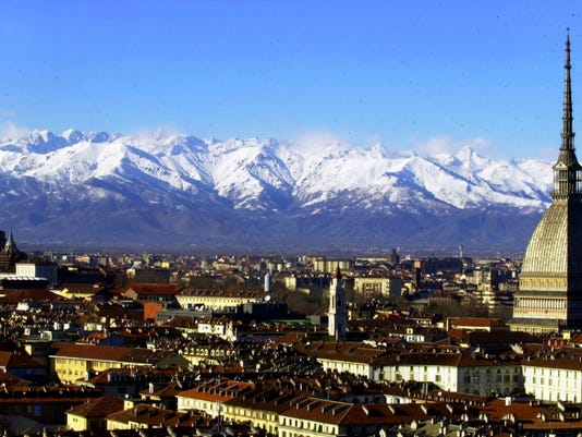 FILE -- A view of Turin, Italy, with the main city landmark, the Mole Antonelliana, at right, and the Alps in background are seen in this December 2005 photo. Milan and Turin are in discussions with the Italian Olympic Committee over a possible bid for the 2026 Winter Games. Turin Mayor Chiara Appendino sent a letter of interest to CONI on Sunday despite divisions in her own party, the populist 5-Star Movement, on a candidacy. (AP Photo/Massimo Pinca)