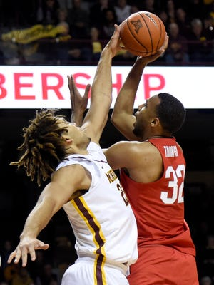 Minnesota center Reggie Lynch (22) blocks a shot by Ohio State center Trevor Thompson (32) of an NCAA college basketball game Sunday, Jan. 8, 2017, in Minneapolis. Lynch was called for a foul on the play.