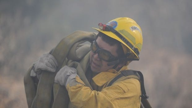 A firefighter carries a hose Jan. 19, 2012, during the Washoe Drive Fire.