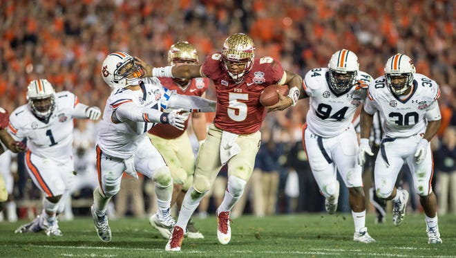 Jameis Winston stiff arms an Auburn defender during a run in the 2013 National Championship.
