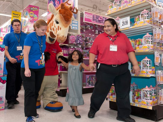 Toys 'R' Us employees walk with cancer survivor Emily Campos, 7, in this file photo from a Make A Wish event at the Visalia Toys R Us.