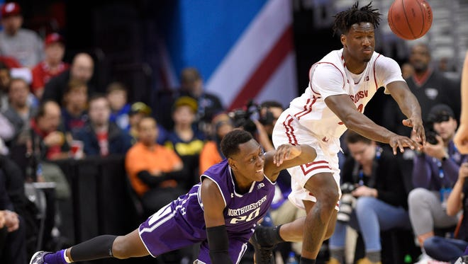 Northwestern guard Scottie Lindsey (20) and Wisconsin forward Nigel Hayes, right, go for a loose ball during the first half of an NCAA college basketball game in the Big Ten tournament on Saturday in Washington, D.C.