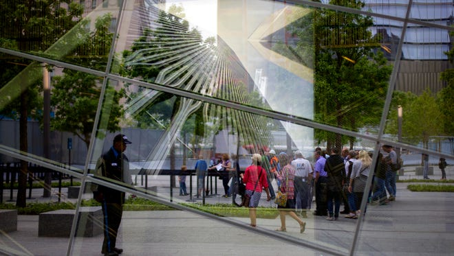 With an image of the former World Trade Center seen through the reflective windows of the 9/11 Memorial Museum, some of the first public visitors are visible arriving at the site in New York in May. Organizers say more than 300,000 people have visited the Sept. 11 museum since it opened little more than a month ago, and that has exceeded their expectations.