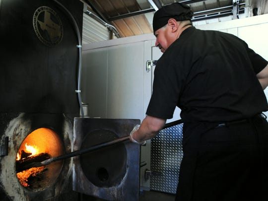 One of around 20 employees at Okie Dokies Smokehouse, Jose keeps the fire going in the smoker, which can hold up to 1,000 pounds of meat, according to owner Steve Dunning.