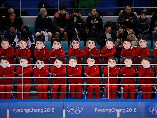 FILE - In this Feb. 10, 2018 file photo, North Korean supporters hold up masks of a handsome young man as they cheer before the preliminary round of the women's hockey game between Switzerland and the combined Koreas at the 2018 Winter Olympics in Gangneung, South Korea. To pour on the charm at the Pyeongchang Olympics, North Korea has turned to ball-gown clad singers, pompom-waving cheerleaders and two of its most influential women -  and the media, the South Korean public and the Olympic audience worldwide seem be to thoroughly enjoy the spectacle. (AP Photo/Jae C. Hong, File)