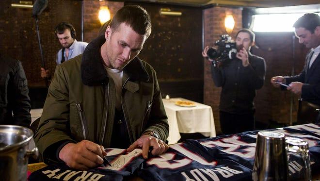 New England Patriots quarterback Tom Brady autographs jerseys at 'A Triumphant Celebration with Living Legend, Tom Brady' on February 8, 2017 in Boston, Massachusetts.