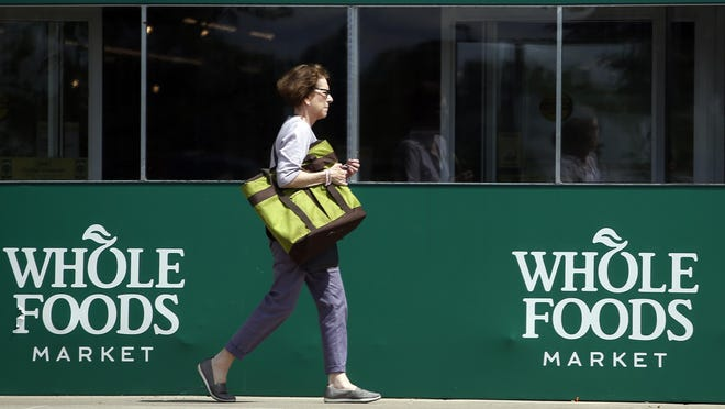 A shopper leaves a Whole Foods Market in Northbrook, Ill., Saturday, June 17, 2017. Amazon is buying Whole Foods in a deal valued at about $13.7 billion, a strong move to expand its growing reach into groceries.